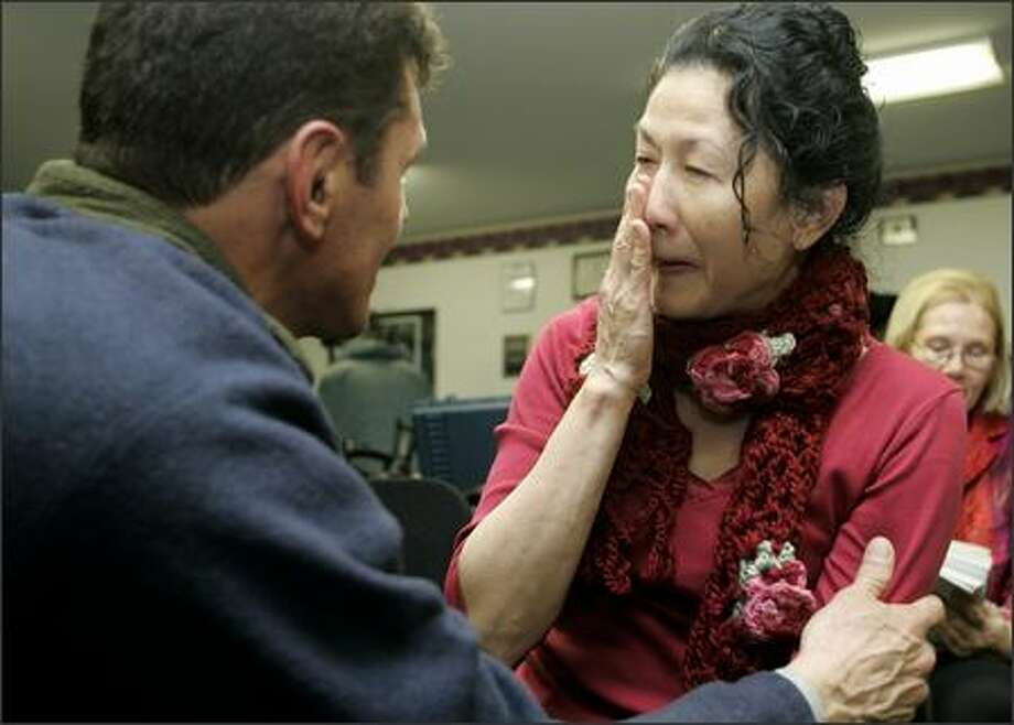 Carolyn Ho, mother of Army 1st Lt. Ehren Watada, sheds a tear as she is hugged by Carlos Arredondo, whose son Alex was killed in Iraq while serving in the Marine Corps, during a news conference in DuPont. Watada's court-martial was ruled a mistrial Wednesday. Photo: / Associated Press