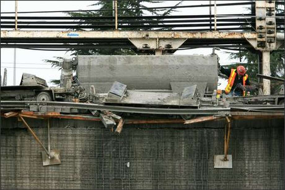 Workers guide a damaged rail car as it's lifted by a crane at Sound Transit's tunnel construction site on Beacon Hill, where one worker was killed in a crash Wednesday. Photo: DAN DELONG/P-I