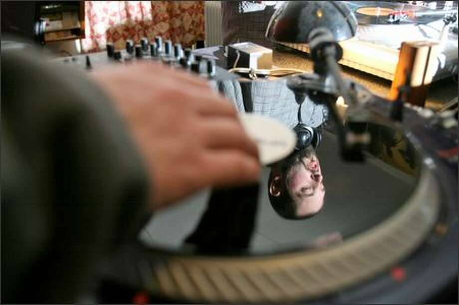 """Ben """"DJ Able"""" Dixon is reflected in a vinyl record as he and his crew scratch out hip-hop music in Dixon's Seattle garage. The Northwest, and Seattle in particular, is the home of a thriving hip-hop scene. Photo: Mike Urban/Seattle Post-Intelligencer"""