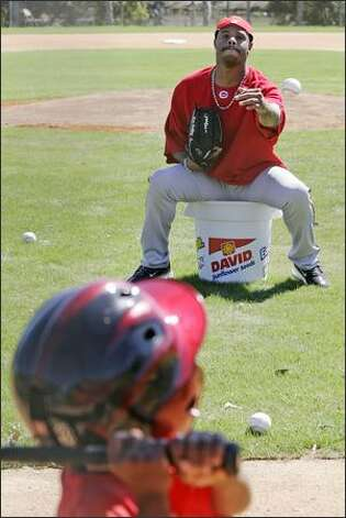 Cincinnati Reds outfielder Ken Griffey Jr. tosses a ball to son Tevin, 4, on Monday at spring training in Sarasota, Fla. Photo: / Associated Press