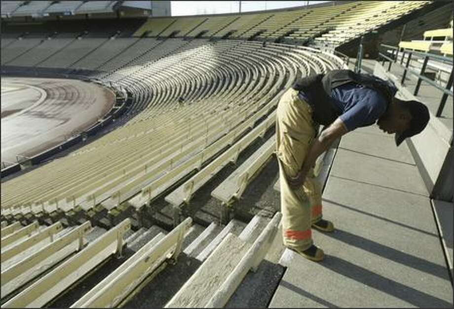 Seattle firefighter Charles Turner pauses for a few breaths before heading back down one of 34 sets of stairs at Husky Stadium in preparation for an upcoming stair-climb race. He and his colleagues have been training twice a week with different combinations of gear and weighted vests. More than 1,200 firefighters from 15 states and as far as New Zealand will race up 69 stories of Seattle's Columbia Center in full gear March 4. The annual climb, the largest individual firefighting competition in the world, raises money for charities. Photo: Andy Rogers/Seattle Post-Intelligencer