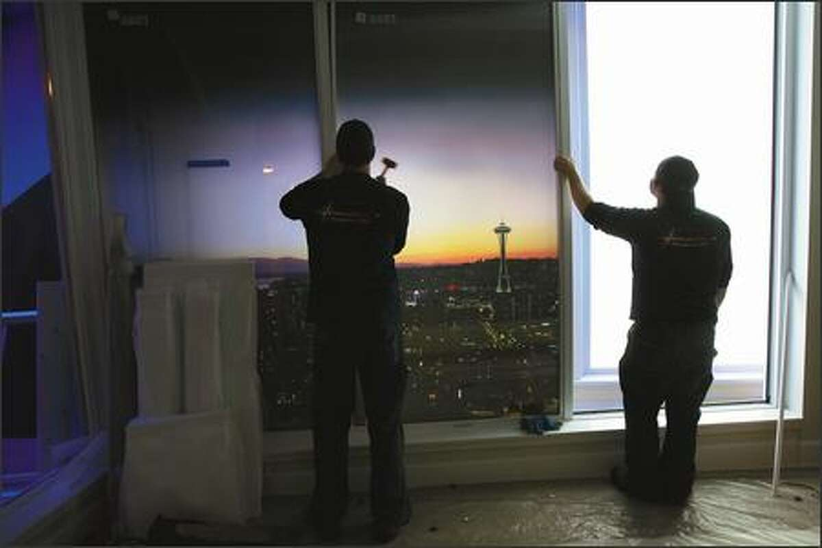 Brian Lukas, left, and Tony Marshlain install a backlighted mural of Seattle as crews put the final touches on a sales center for the ESCALA condos to be built in Belltown.