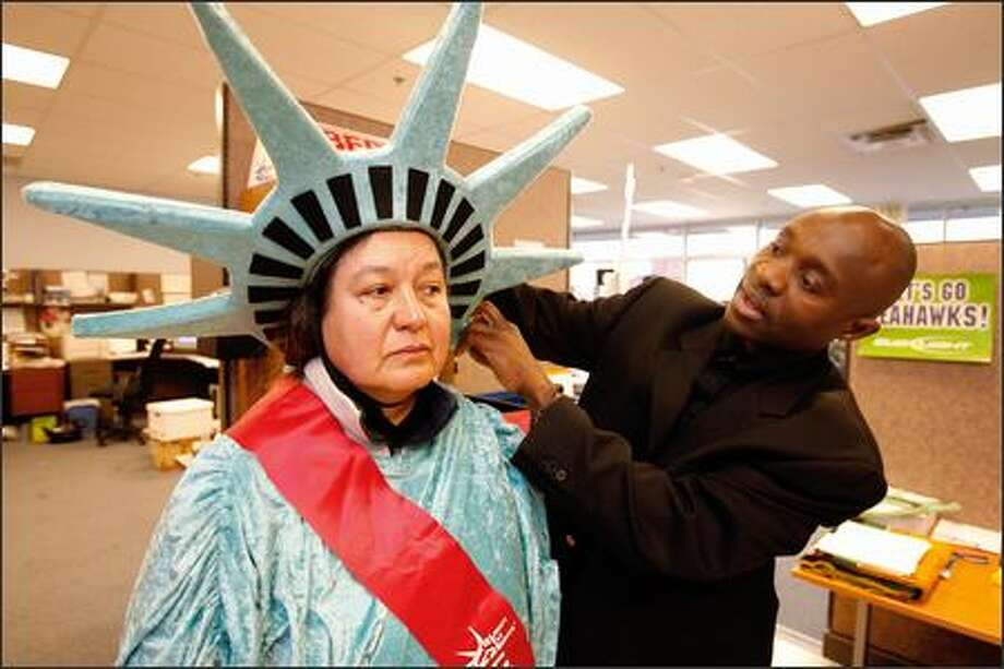Liberty Tax Service franchise owner Jean-Claude Valsaint helps Maria Del Villar Lopez with her Lady Liberty costume at his office in Burien. A homeless woman he offered a job to has yet to take his offer. Photo: Gilbert W. Arias/Seattle Post-Intelligencer