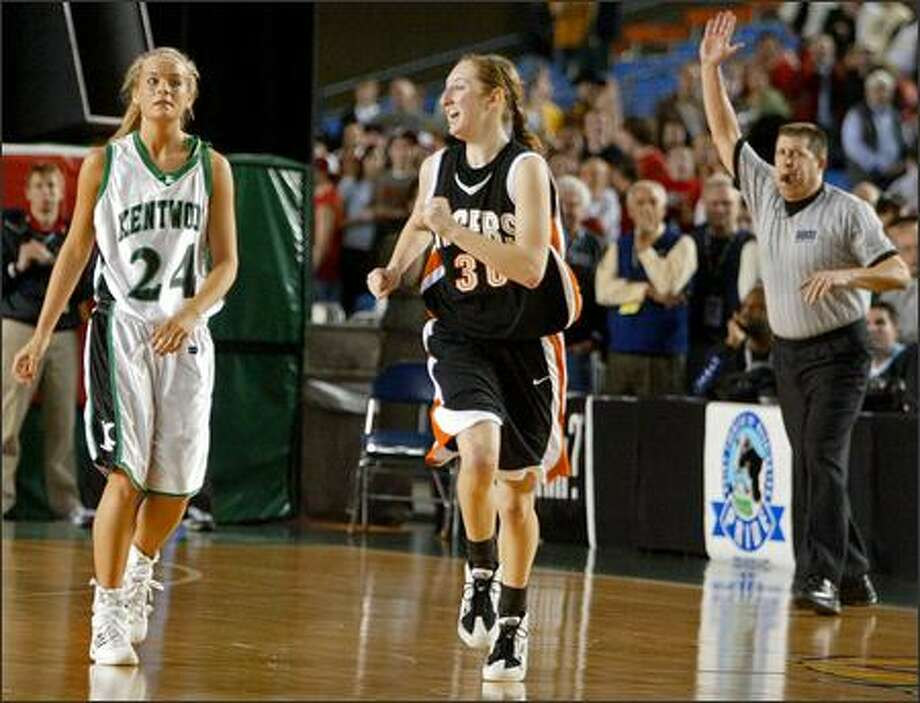 Lewis & Clark's Lyndi Seidensticker runs up the court after sinking the game-winning 3-pointer as Kentwood's Jessica Rodgers looks on in disbelief. Photo: Mike Urban/Seattle Post-Intelligencer