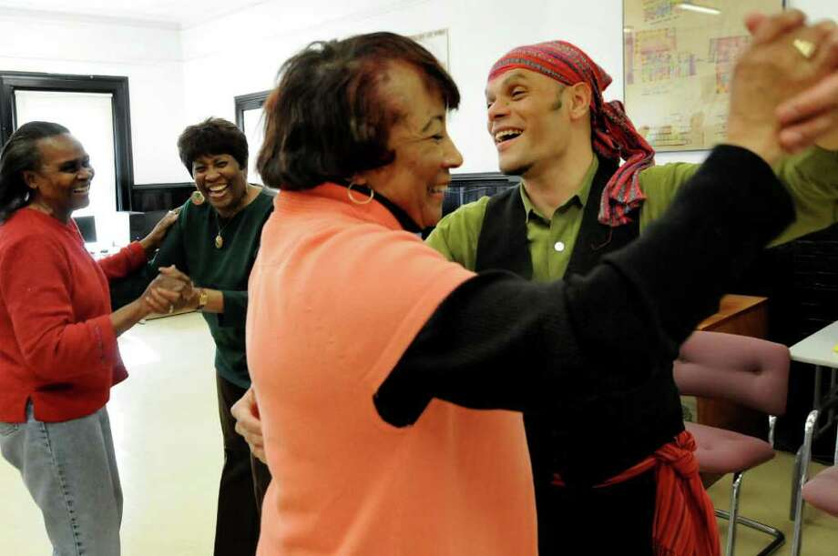 Dance instructor Carlow Osorio, right, dances the merengue with Lartharee Jones, center, while Stella Bess, left, pairs up with Loretta Brown during the Dancing with our Elders program on Wednesday, March 16, 2011, at Trinity Alliance in Albany, N.Y. The program provides exercise, fun and socialization for people over 55-years old. (Cindy Schultz / Times Union) Photo: Cindy Schultz