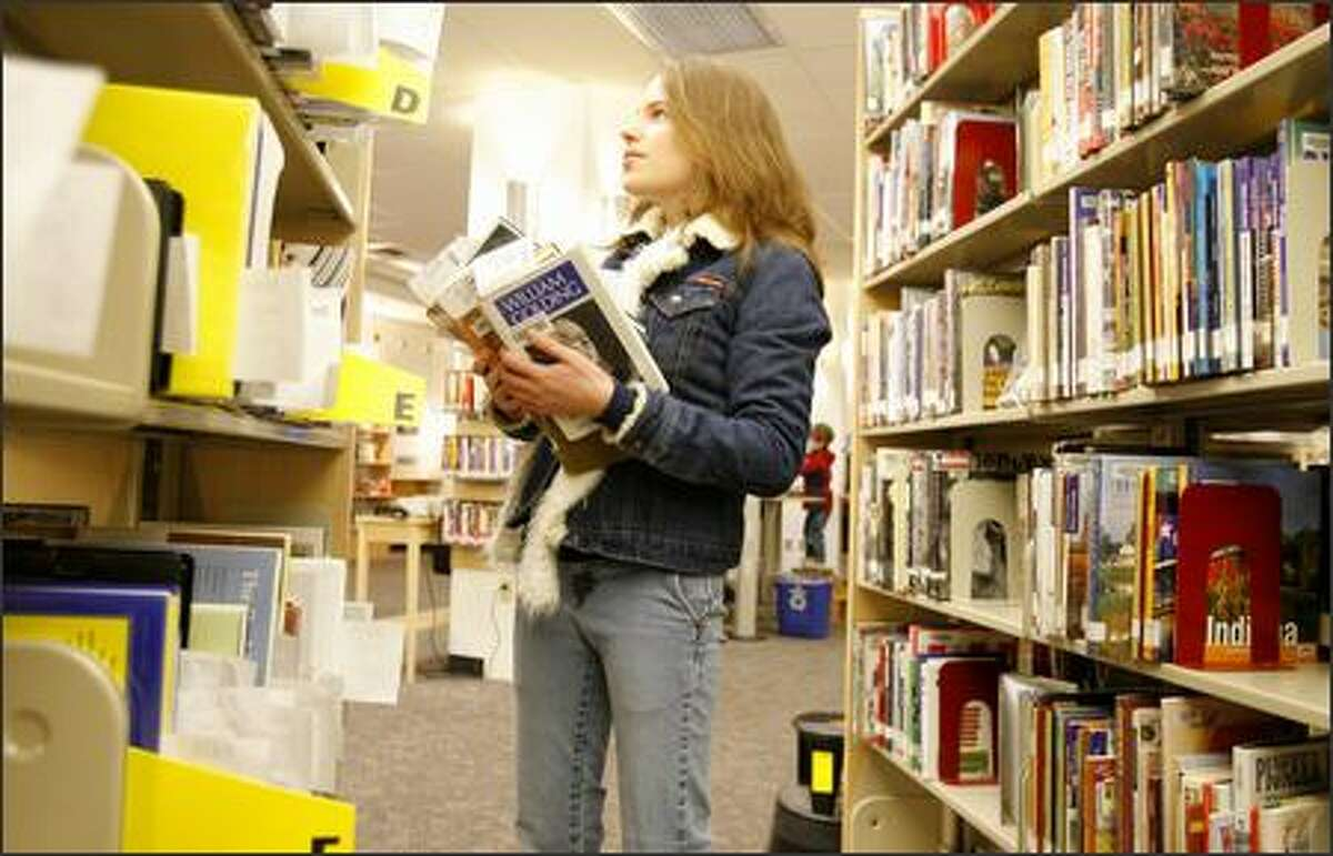 Leslie Cornaby, 16, a sophomore at Shorecrest High School picks up a load of books at the Lake Forest Park Library on Thursday.