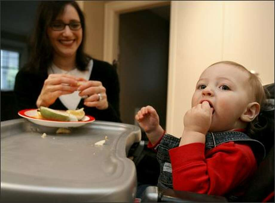 Lori Heller feeds an afternoon snack of banana, orange and cheese to her 15-month-old son, Benjamin Wintraub, at their home in Seattle. Photo: P-I Photo