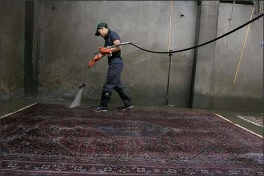Employee Ket Hormthoum washes a rug at Emmanuel's Rug & Upholstery Cleaners in Seattle. The company has been in business since 1907. Photo: Meryl Schenker/Seattle Post-Intelligencer