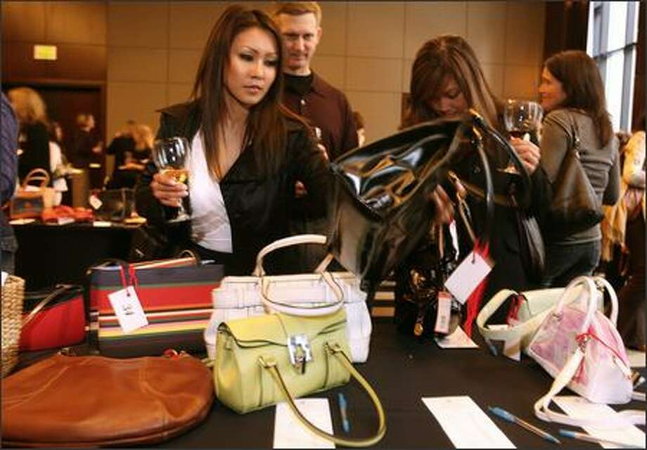 Jenna Dolkar, left, and Melody Pacheco, right, check out purses while Kevin Kelly, center, watches. Kelly would later buy a purse for $550 during the live auction Sunday at the Bags, Baubles and Bottles auction for Gilda's Club in Seattle. Photo: Grant M. Haller/Seattle Post-Intelligencer