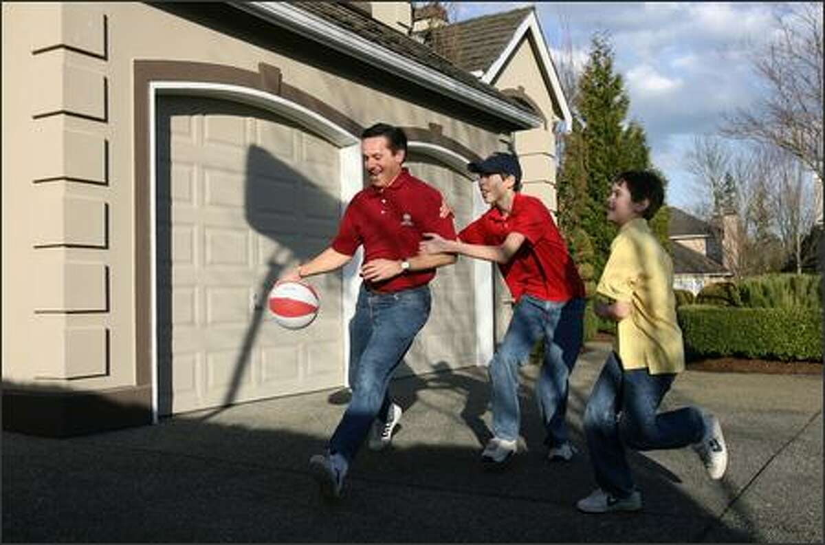 Dino Rossi is fouled by his son, Jake, 13, while his other son, Joseph, 10, runs to get in on the action as they shoot hoops in the driveway of their Sammamish home.