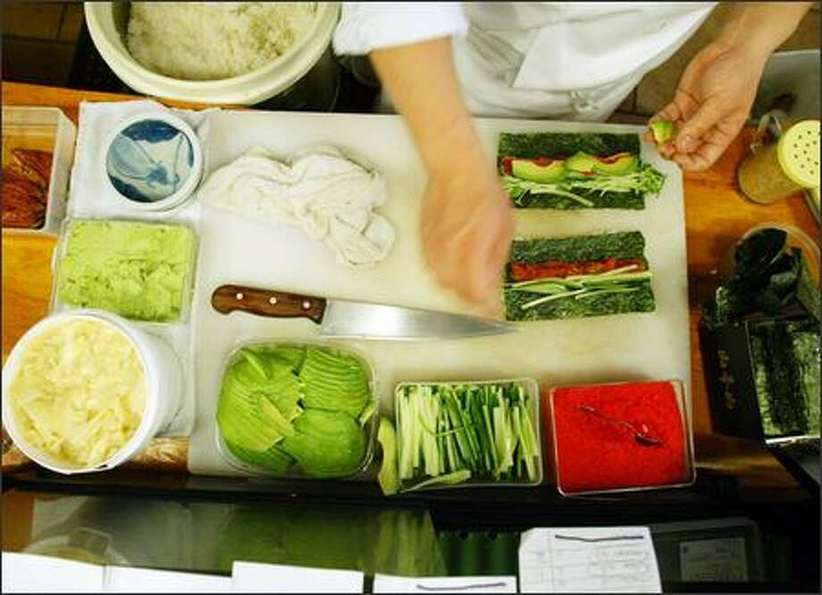 Taichi Kitamura makes a Fishmonger roll from salmon and vegetables. Photo: Paul Joseph Brown/Seattle Post-Intelligencer