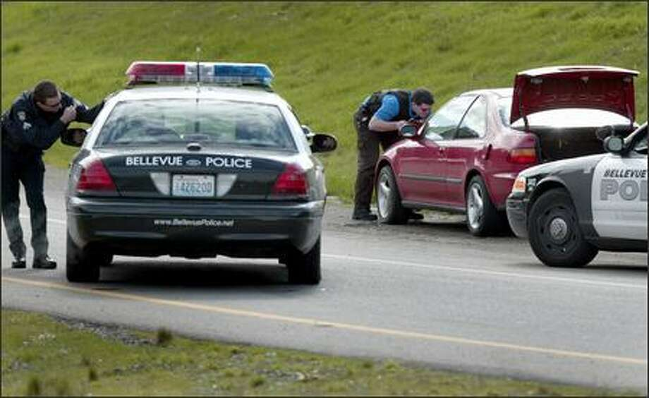 Police investigate the scene on the Interstate 405 onramp where a car came to rest after Bellevue motorcycle officers shot at a suspect in a bait car that was stolen Wednesday. The suspect was captured nearby. The shooting and investigation slowed traffic to a crawl all afternoon on I-405. Photo: Joshua Trujillo/Seattle Post-Intelligencer