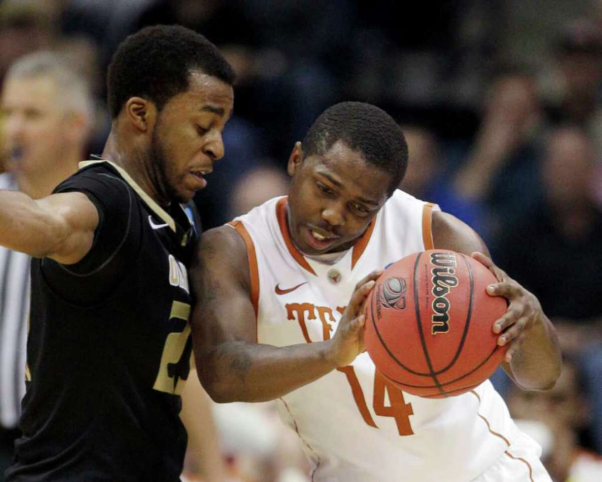 Texas guard J'Covan Brown is defended by Oakland, Mich. guard Reggie Hamilton in the second half of a West Regional NCAA tournament second round college basketball game, Friday, March 18, 2011 in Tulsa, Okla. Texas won 85-81.