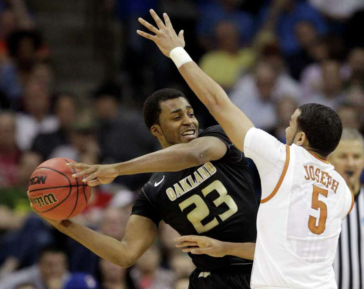 Oakland, Mich. guard Reggie Hamilton tries to pass around Texas guard Cory Joseph in the first half of a West Regional NCAA tournament second round college basketball game, Friday, March 18, 2011 in Tulsa, Okla.