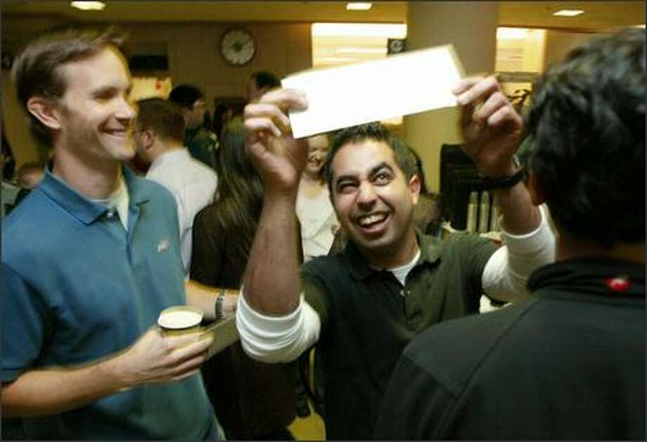 """Adi Dabestani, 30, eyes the envelope that he said was holding his destiny -- the medical residency program he was """"matched"""" with after finishing at the University of Washington medical school. Dabestani, who grew up in Marysville, was matched with the UW Medical Center, one of his top choices. At left is Erik Brand, one of Dabestani's roommates who had also just received an envelope containing his match. Photo: Paul Joseph Brown/Seattle Post-Intelligencer"""