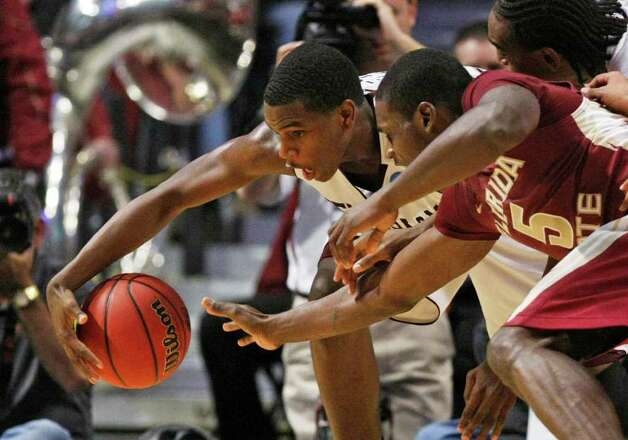 Texas A&M's Khris Middleton (22) and Florida State's Bernard James (5) scramble for a loose ball in the second half of a second-round NCAA Southwest Regional tournament college basketball game in Chicago, Friday, March 18, 2011. Florida State won 57-50. Photo: AP Photo/Charles Rex Arbogast