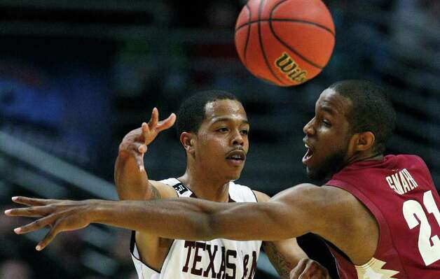 Texas A&M's B.J. Holmes passes the ball past Florida State's Michael Snaer (21) in the first half of a second-round NCAA Southwest Regional tournament college basketball game in Chicago, Friday, March 18, 2011. Photo: AP Photo/Charles Rex Arbogast