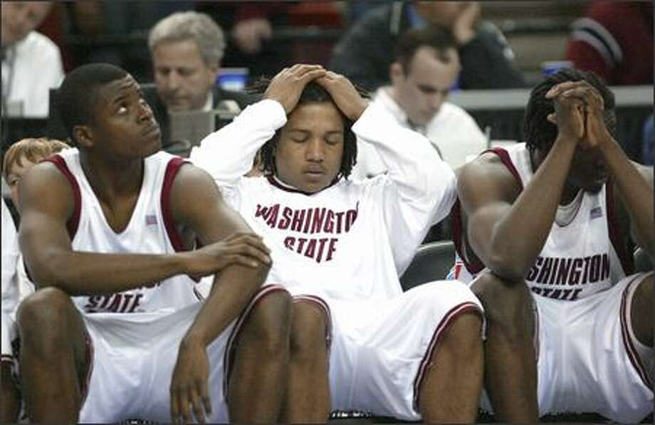 From left, Washington State's Chris Matthews,Jeremy Cross and Ivory Clark watch the closing seconds of their 78-74 double-overtime loss to Vanderbilt in the second round of the NCAA tournament in Sacramento, Calif. Photo: / Associated Press