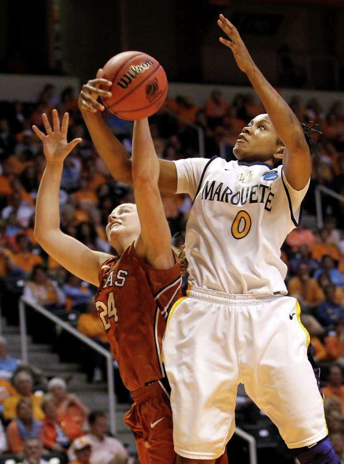Marquette forward Jasmine Collins (0) takes a rebound away from Texas guard Chassidy Fussell (24) during the first half of a first round game in the NCAA women's college basketball tournament on Saturday, March 19, 2011, in Knoxville, Tenn.