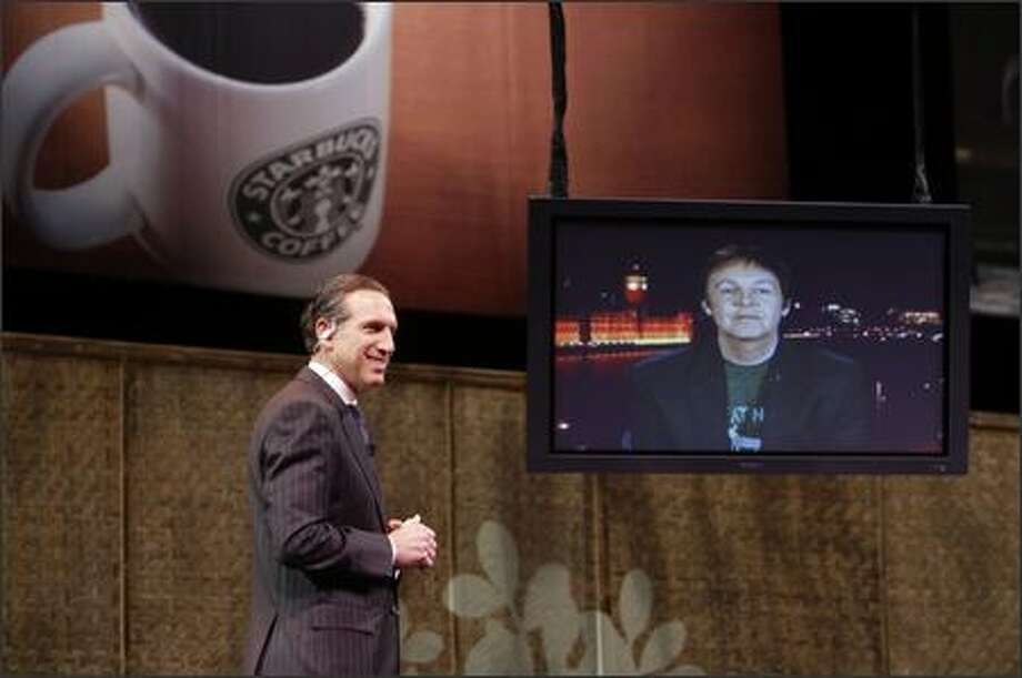 Starbucks chairman Howard Schultz speaks with Paul McCartney via a satellite feed during the company's annual shareholders meeting at McCaw Hall in Seattle Wednesday. McCartney is the first artist signed to the recently announced Starbucks record label. Photo: Andy Rogers/Seattle Post-Intelligencer
