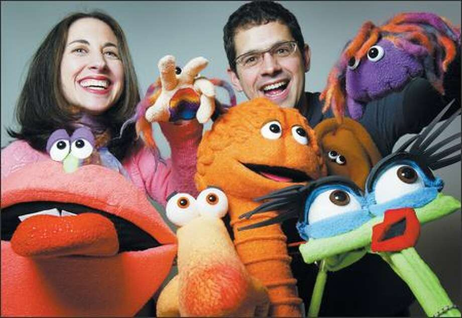 """Husband and wife team Sam Reich-Dagnen and Johnny Dagnen have fun with some of Braincandy's stars. In the company's DVD """"My 5 Senses,"""" the colorful puppets, including Mojo Mouth, Harry Hand, Nusi Nose, Bruce Brain, Ana Ear and Ivy Eyes, guide young children in an exploration of their senses. Photo: Joshua Trujillo/Seattle Post-Intelligencer"""