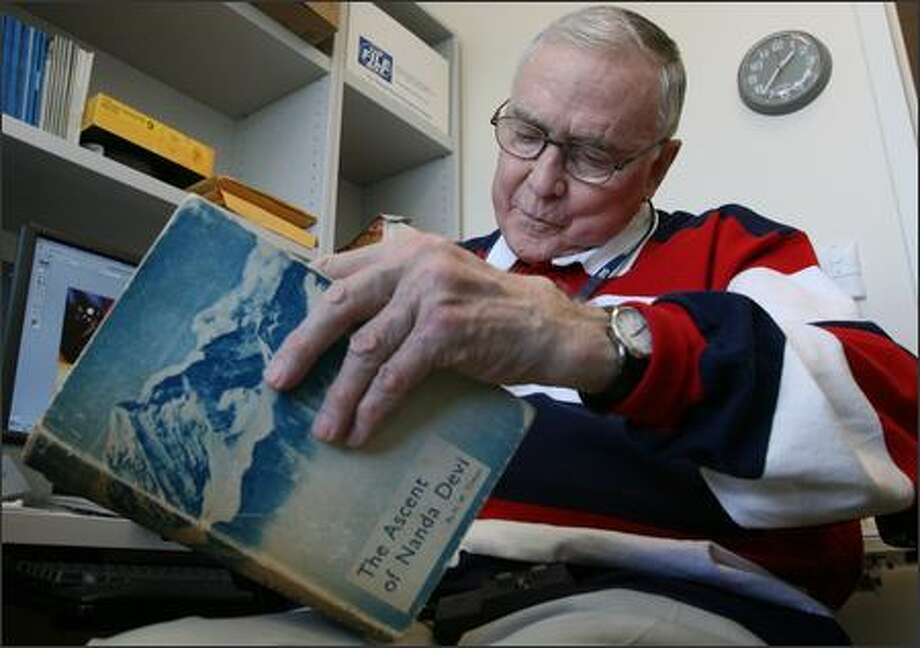 "Robert Schaller, a former pediatric surgeon who still teaches at Children's Hospital and Regional Medical Center in Seattle, looks over a copy of ""The Ascent of Nanda Devi."" In 1965, Schaller tried to scale the peak to install a listening device that never made it to the top. Photo: Grant M. Haller/Seattle Post-Intelligencer"