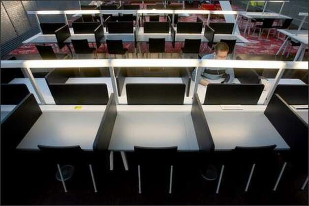 Cliff Barnard studies in the 10th-floor reading room, which is badly designed and cheesily detailed, including drab plastic study cubicles. Photo: Mike Urban/Seattle Post-Intelligencer