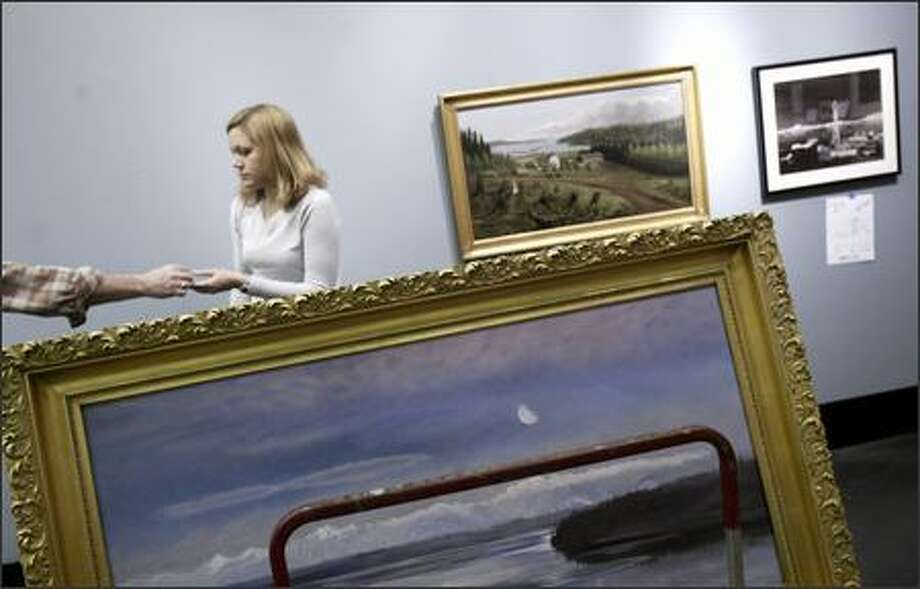 """Julie Baron, designer of the new Museum of History and Industry exhibit """"Nature in the Balance,"""" prepares to hang """"Panoramic View of the Olympic Mountains"""" by Emily Inez Denny, a daughter of Seattle settler David Denny. Photo: Andy Rogers/Seattle Post-Intelligencer"""
