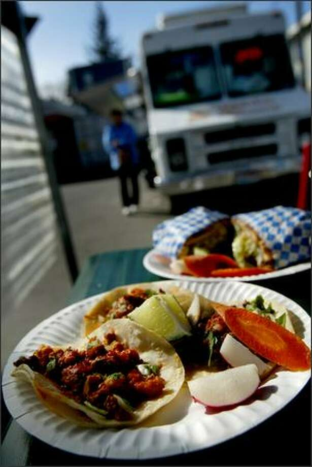 Birria (spicy Mexican meat stew) and tripe tacos, in the foreground, and a chicken torta plate from the Taqueria El Rincon taco truck in South Park. Photo: Joshua Trujillo/Seattle Post-Intelligencer