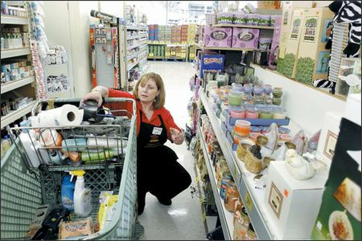 Debbi Mullen, who co-owns the Rainier Grocery Outlet in Seattle with her husband, Steve, works in the store aisle Tuesday. The Mullens also own the Madrona Grocery Outlet. They are gambling that they can turn a profit in Rainier Valley when the light rail system opens.