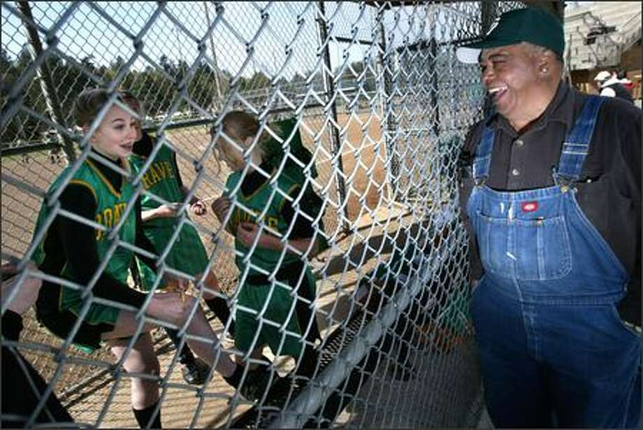 "George Hildreth (with, from left, Bishop Blanchet High School softball players Maddie Barton, Melissa Gomez and Becca Wirta) says of his volunteer work, ""As long as it's for the kids, I have the energy."" Photo: Andy Rogers/Seattle Post-Intelligencer"