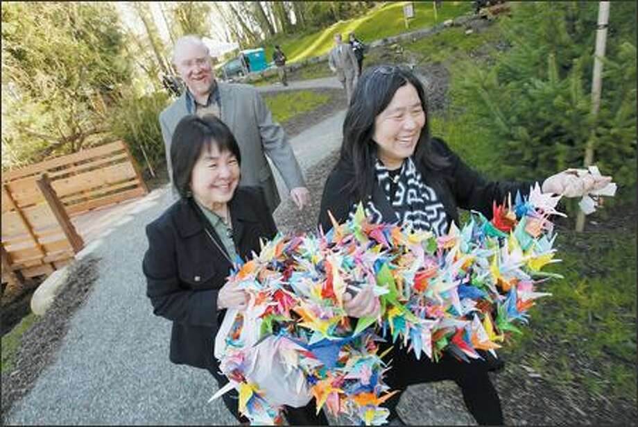 Jan Buday, left, and Karen Matsumoto carry strings of cranes to hang during a commemoration ceremony Friday at the new Nidoto Nai Yoni Memorial on Bainbridge Island. John Buday, behind, designed parts of the memorial, which recognizes the Japanese Americans taken to internment camps in 1942. Photo: Andy Rogers/Seattle Post-Intelligencer