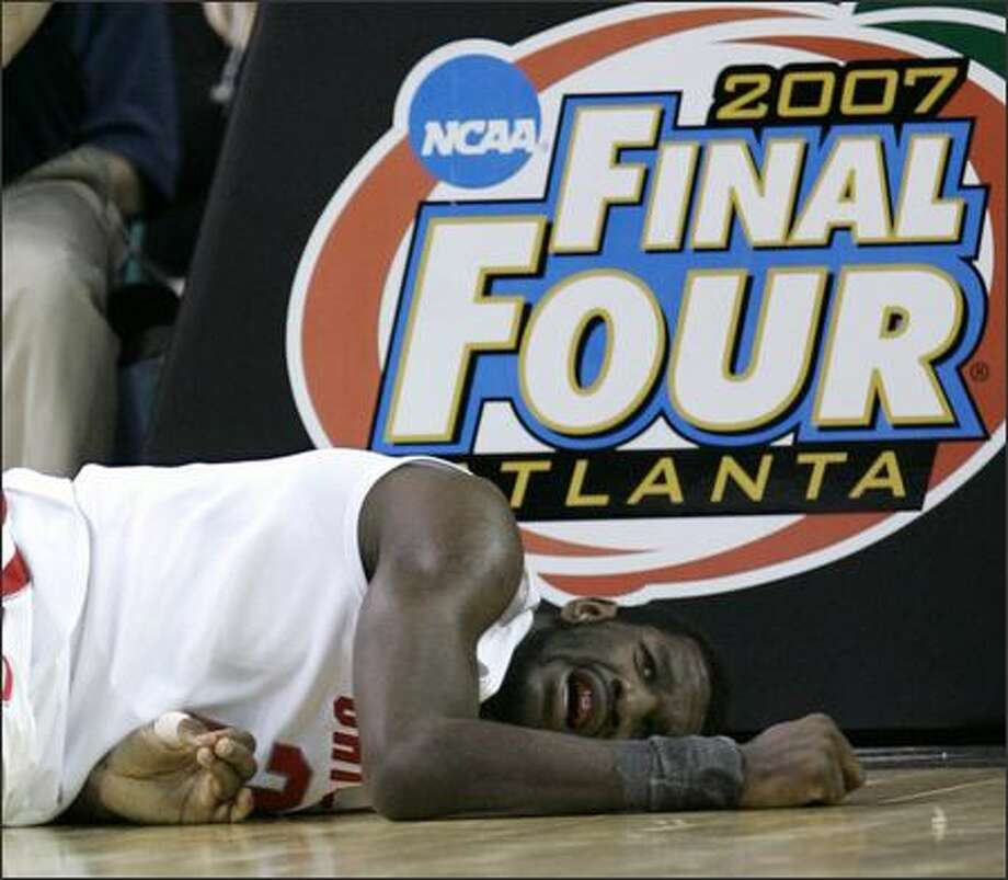 Ohio State center Greg Oden lies on the court after dunking a basket and falling during the second half of a Final Four semifinal game against Georgetown. The Buckeyes won 67-60 to advance to their first national championship match in 45 years.  (AP Photo/Eric Gay) Photo: /Associated Press