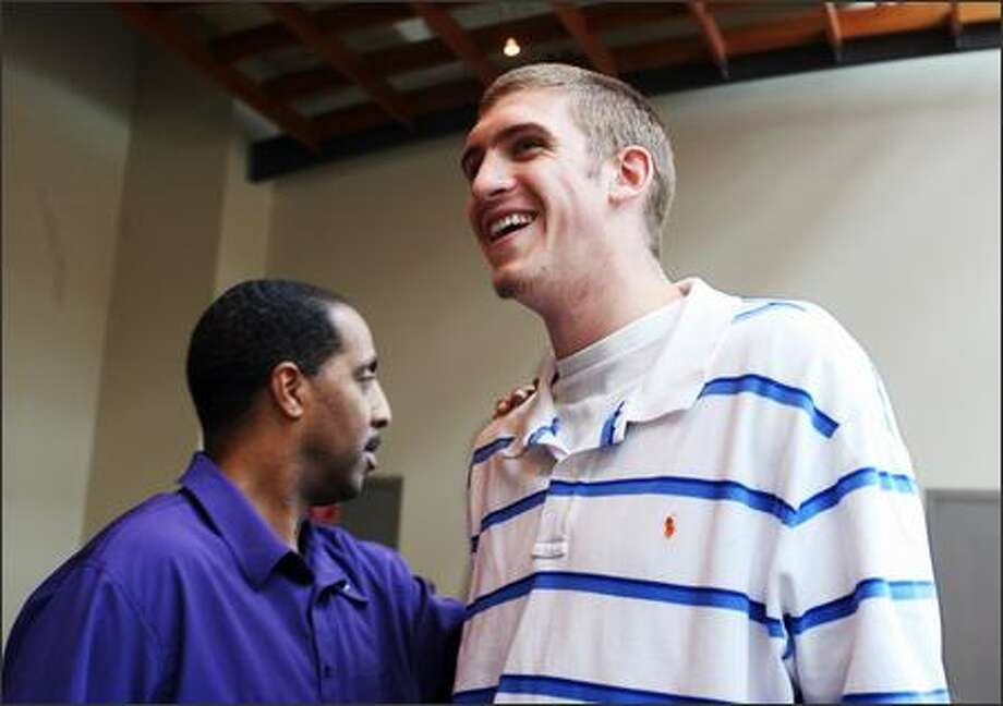 University of Washington freshman center Spencer Hawes talks with head coach Lorenzo Romar just prior to announcing his intentions to enter the NBA draft, but will not hire an agent, so that he can pull his name out of the draft and come back to school if he wants. Photo: Scott Eklund/Seattle Post-Intelligencer
