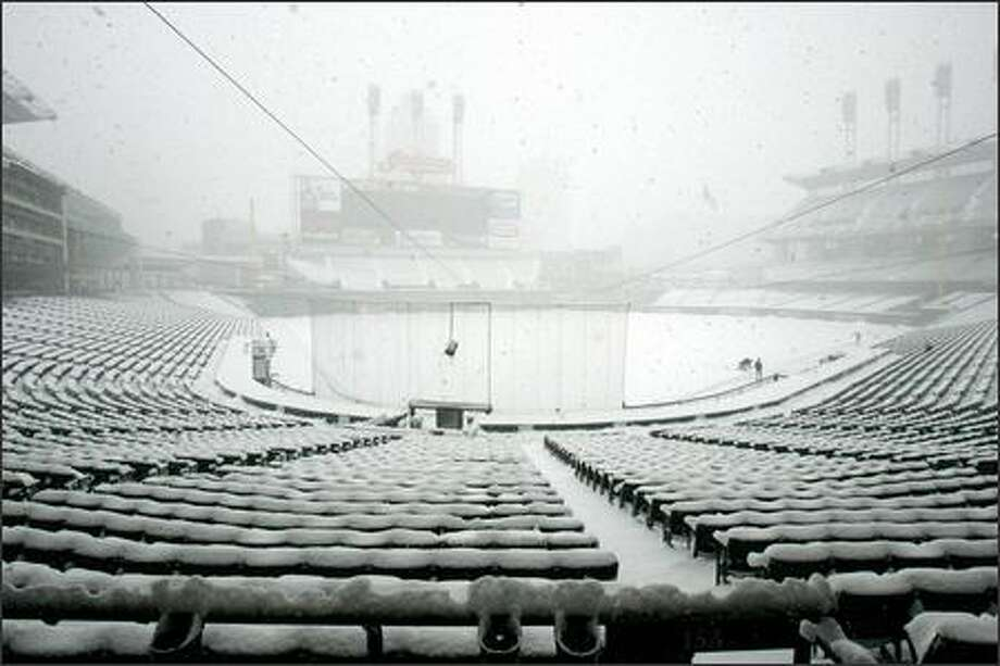 Jacobs Field in Cleveland is empty except for a few Mariners playing in the snow. Snow continued to fall throughout the day Sunday. Photo: / Associated Press