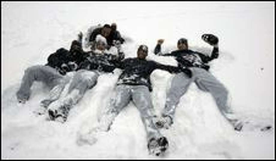 Third base coach Carlos Garcia, top, supervises as, from left, Jose Vidro, Jose Lopez, Adrian Beltre and Richie Sexson play in the snow. Photo: / Associated Press
