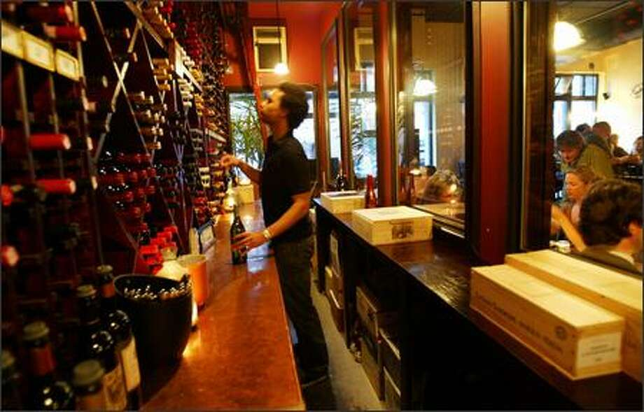Devin Hampton searches for a bottle of wine at Bricco della Regina Anna in the climate-controlled wine cellar. The extensive wine covers Washington, Italy, France, Portugal, Spain and South Africa. Photo: Joshua Trujillo/Seattle Post-Intelligencer