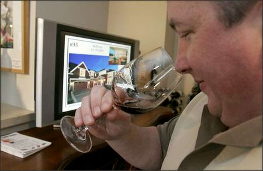 Jeff Jones of Kirkland sniffs a wine before tasting it at Windermere Real Estate's new Living Room office in Kirkland, which offers wine tasting and art for sale, as well as opportunities to view homes. Jones found out about the event on a wine-tasting Web site. Photo: Meryl Schenker/Seattle Post-Intelligencer