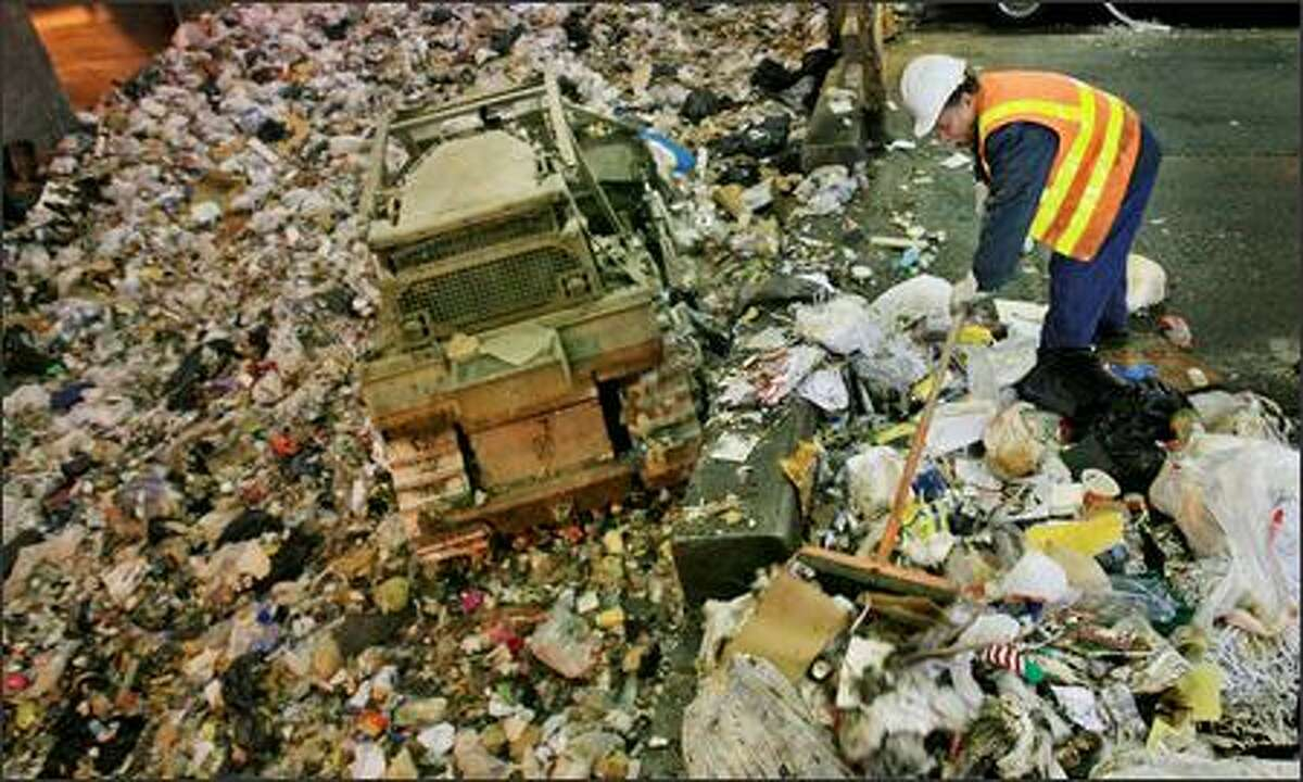 A worker pushes trash into the pit at the Seattle Public Utilities South Recycling and Disposal Station. The city is considering aggressive changes to its recycling rules.