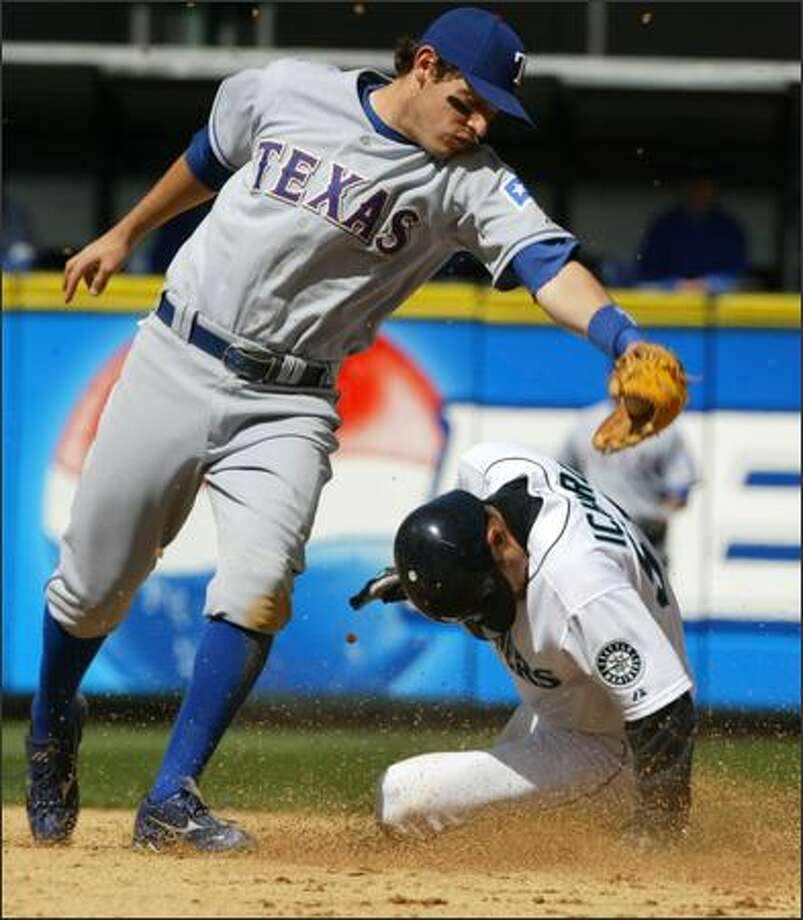 Texas Rangers second baseman Ian Kinsler is unable to put a tag on Ichiro Suzuki as he steals second base in the fourth inning. It was the first successful steal for the Mariners this season and the 40th consecutive successful steal for Ichiro.  (Andy Rogers/Seattle Post-Intelligencer) Photo: Andy Rogers/Seattle Post-Intelligencer