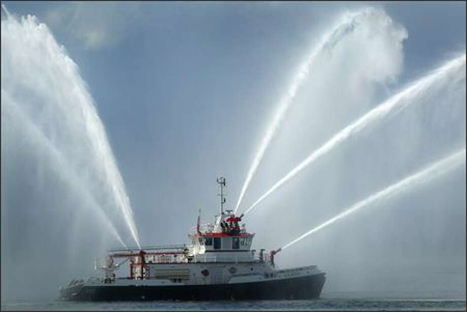 The new fireboat Leschi demonstrates some of its capabilities Tuesday as it approaches its new home, Station 5, on the waterfront in Seattle. It was paid for by the Fire Facilities and Emergency Response Levy approved in 2003. Photo: Joshua Trujillo/Seattle Post-Intelligencer