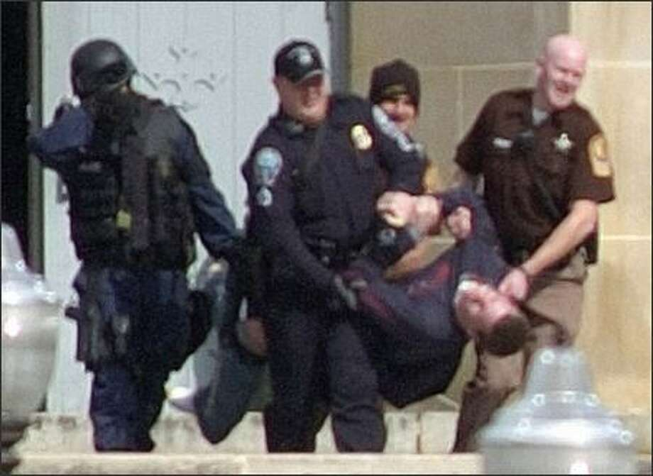 In this photo, a version of which ran on the front page of Tuesday's P-I, shooting victim Collin Goddard is carried from Norris Hall at Virginia Tech. Photo: / Associated Press