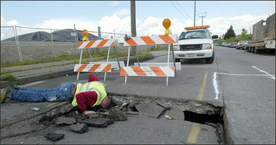 John Taylor of Puget Sound Energy contractor Central Locating Service tries to see whether a gas line was damaged by a sinkhole on the 6700 block of Corson Avenue South near East Marginal Way. Photo: Karen Ducey/Seattle Post-Intelligencer