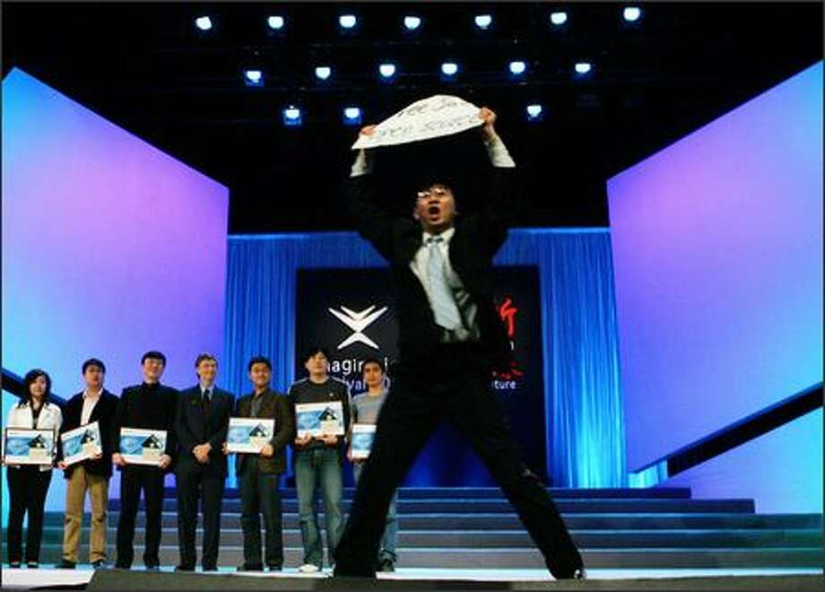 "An unidentified demonstrator flashes a sign reading ""Free software, Open source"" as he rushes across the stage following a speech by Microsoft Chairman Bill Gates -- standing in the middle of teh group at the rear -- in Beijing.  (AP Photo/Elizabeth Dalziel) Photo: / Associated Press"