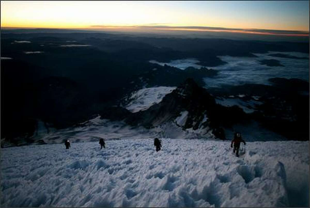 Climbers inch their way toward the summit of Mount Rainier just before sunrise. A typical summit trip led by RMI leaves Camp Muir at about 1 a.m. and reaches the top around 8 a.m.