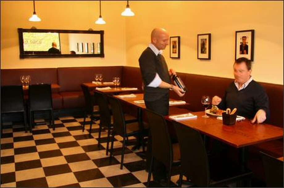 "With its black-and-white tile floor and spare furnishings, La Buca looks like a ""simple neighborhood trattoria."" But it draws raves for its classic Italian food. Photo: Janice Mucalov - Special To The Seattle Post-Intelligencer /"