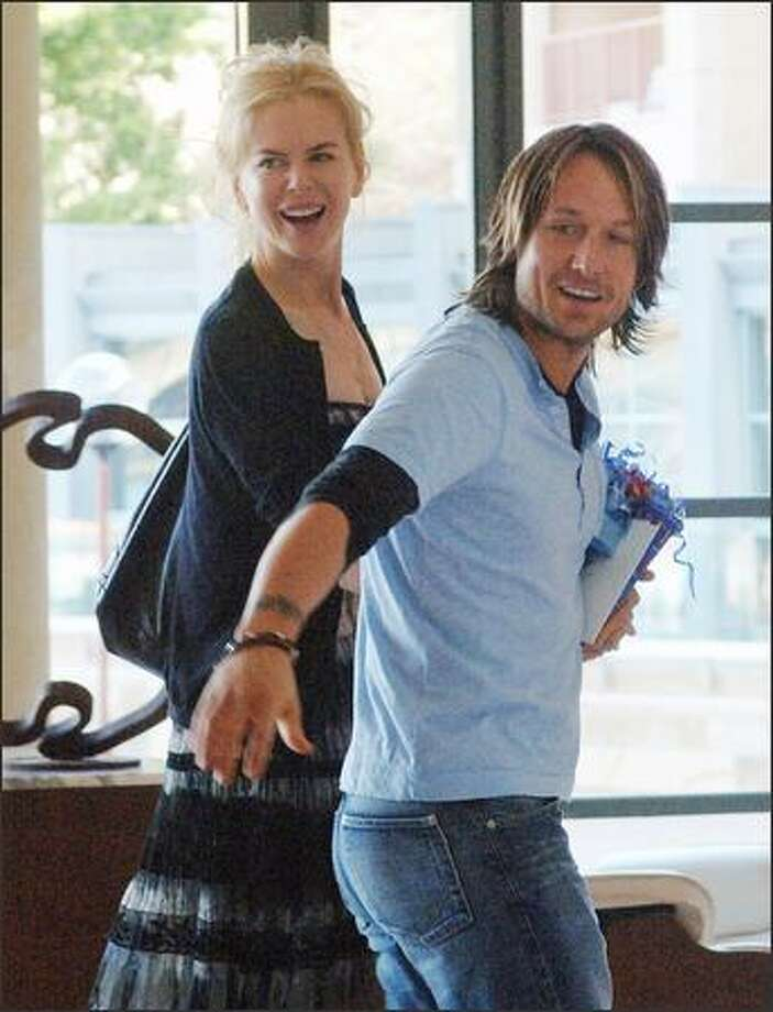 Australian actress Nicole Kidman, left, walks with her husband and Australian country music singer Keith Urban through the lobby of a hotel in Sydney, Australia, Monday. Photo: / Associated Press