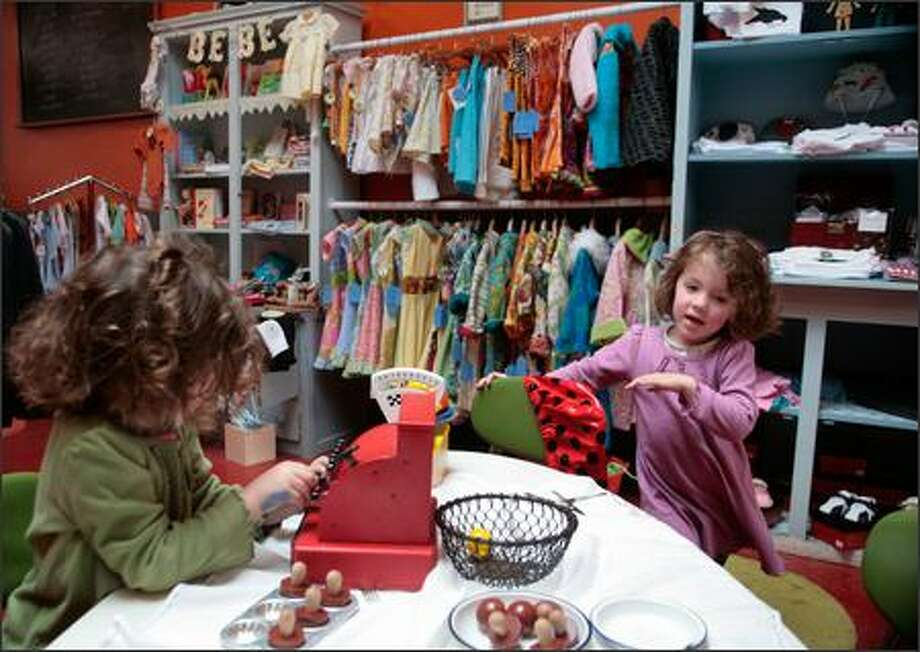Twins Madelyn and Tess Turner, 4, entertain themselves in the children's play area of Retroactive Kids while their mothers shops. Photo: Meryl Schenker/Seattle Post-Intelligencer