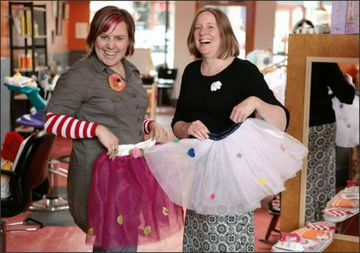 Beth Reyes, left, and Trisha Gilmore, co-owners of Retroactive Kids,show off tutus they sell in their store which they advertise as