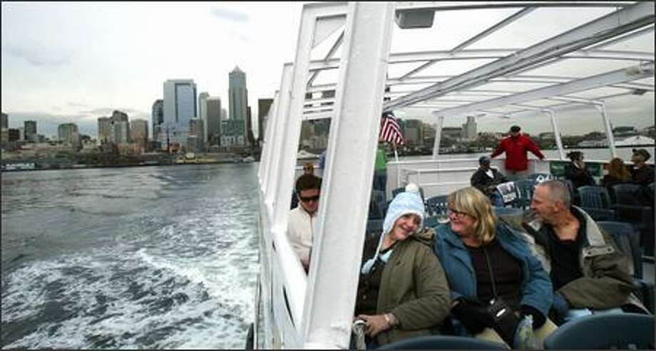 Alana Paul, left, and family members Sue and Chris Paul, all visiting from Australia, take the Elliott Bay Water Taxi to West Seattle on Monday. Photo: Karen Ducey/Seattle Post-Intelligencer
